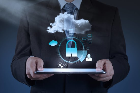 A man holds a tablet. Above the tablet floats a cloud and a lock and some other symbols, indicating cloud application security